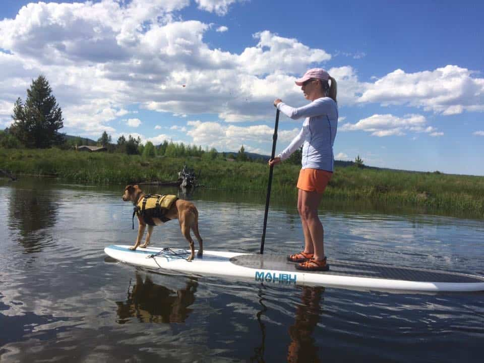 Cathy Eason Paddle Boarding with Her Dog
